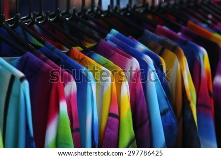 cloth in shop, shirt and dress in shop, shirt and dress,through new clothes during shopping,Colorful man and woman's dresses on wood hangers in a retail shop. Fashion and shopping business concept.  - stock photo