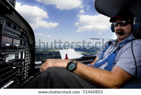 co-pilot flying small aircraft with clouds in background - stock photo