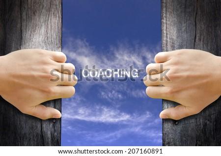 """coaching"" text in the sky behind 2 hands opening the wooden door. - stock photo"
