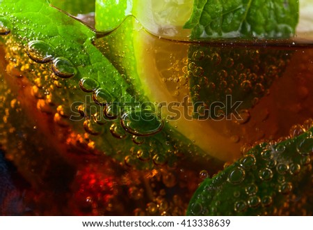 cocktail Cuba libre with lime , ice  and peppermint leaves  - stock photo