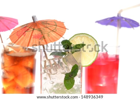 cocktail in wineglasses with lime, mint and umbrella - stock photo