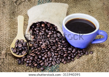 coffee cup and coffee beans on burlap textile and brown background. - stock photo