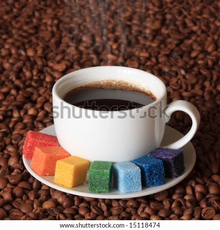 """Coffee for an artist"" Smoking cup of coffee with  colorful sugar, on coffee beans background - stock photo"
