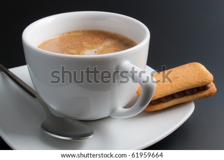 Coffee. White porcelain cup of freshly brewed coffee arranged with plate, spoon and sandwich-biscuit with chocolate isolated on dark gray background - stock photo