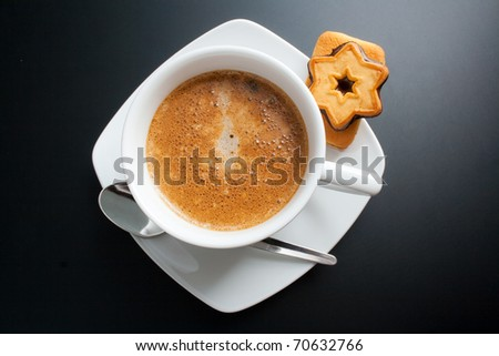 Coffee. White porcelain cup of freshly brewed coffee top view close-up arranged with two sandwich-biscuits, spoon and plate on dark background - stock photo
