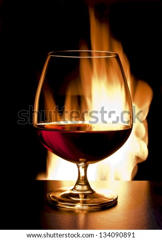 cognac and fire on black background - stock photo