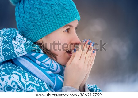 cold winter. portrait girl in a blue cap and jacket warms her hands