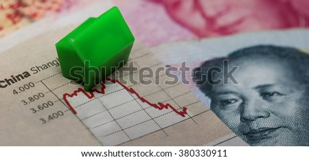 (Collapsed) house on top of a stock market graph next to a Chinese banknote (showing Mao). Red downtrend indicates the stock market recession period - stock photo