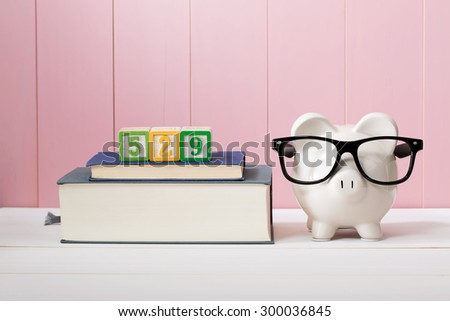 529 college savings and paying for education concept with piggy bank wearing eyeglasses alongside textbooks  - stock photo