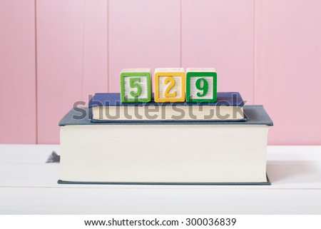 529 college savings plan concept with textbooks stacked in front of a pink wooden background with copyspace - stock photo