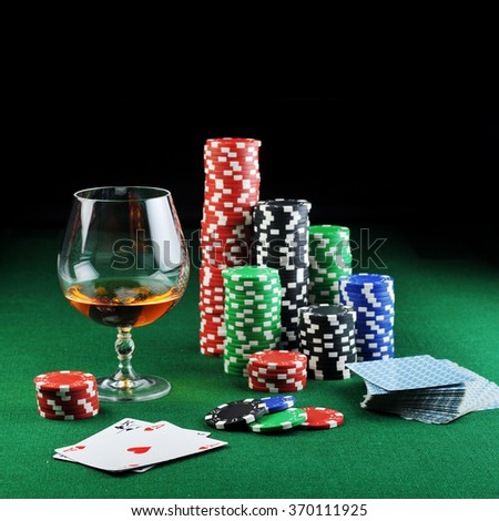 color chips for gambling, drink and playing cards on green - stock photo