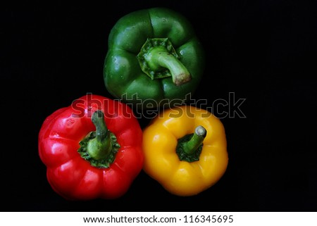 3 colored capsicum red, green and yellow with black background