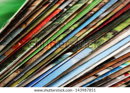 Colorful abstract background image of stacked magazines with slightly worn edges. Macro with extremely shallow dof. - stock photo