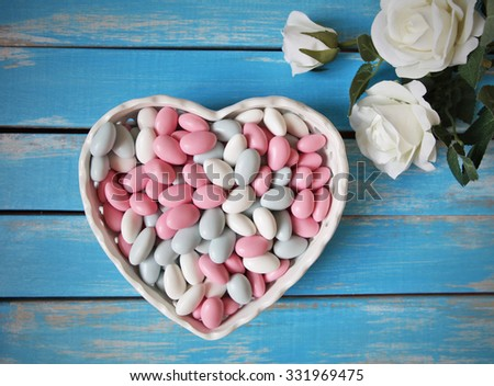 Colorful candy in white heart shaped bowl and white roses  on wooden table .Top view from above  - stock photo