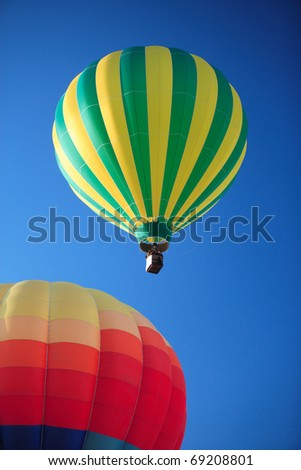 2 colorful hot air balloons floating lazily away on a vibrant blue sky. - stock photo