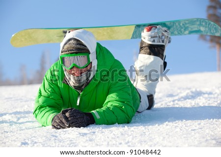 colorful image of young snowboarder in green jacket lying on the snow - stock photo