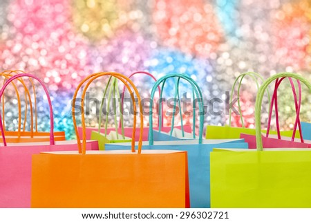 colorful paper shopping bags against glitter background - stock photo