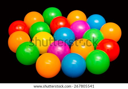 colorful plastic balls on black background - stock photo
