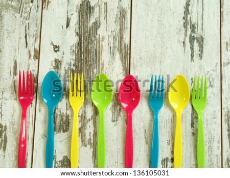 colorful plastic tableware on wooden boards