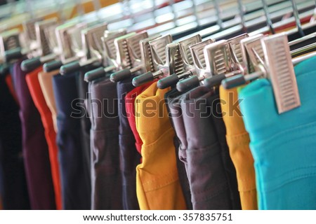 colorful trousers with hanger on rack , cloths shop in shopping mall , colorful fabric and fashion clothes background