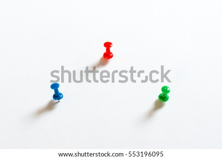 3 coloured thumbtack pins with shadows on white background with paper structure