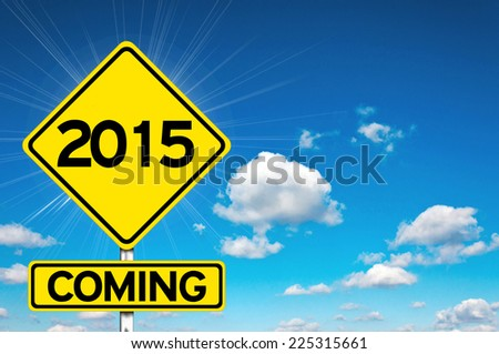 2015 coming sign yellow road sign with clouds and sky in background