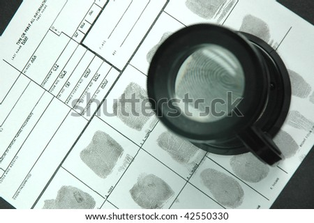 comparing the fingerprint through the  magnifier glass - stock photo