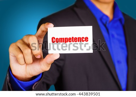 """""""Competence"""" black and red text on white card hold by young business man wearing a business jacket - economic, finance and crisis concept - stock photo"""