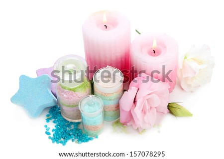 Composition with aromatic salts in glass bottles, candles and flower, isolated on white - stock photo