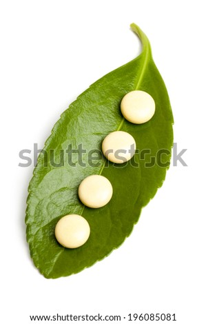 Concept of alternative medicine: Homeopathic natural pills on the leaf isolated on white background - stock photo