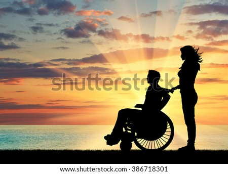 Concept of disability and disease. Silhouette of disabled person with a guardian on the sea sunset