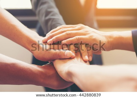 Concept of teamwork: Close-Up of hands business team showing unity with putting their hands together. - stock photo