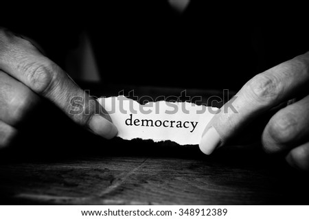 Concept woman with message on paper in hands - democracy - stock photo