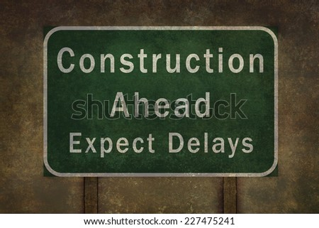 """""""Construction ahead expect delays"""" roadside sign illustration, with distressed ominous background - stock photo"""
