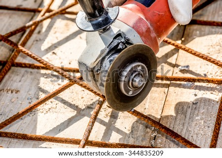 Construction Worker cutting construction  stee netl with Angle Grinder Mashine closeup