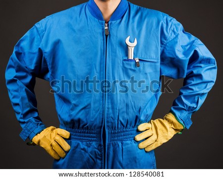 Construction worker with wrench in his pocket against gray background - stock photo