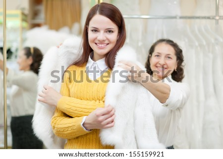 consultant helps girl chooses fur cape at shop of wedding fashion. Focus on bride - stock photo