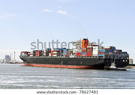 container ship and pilot boat - stock photo