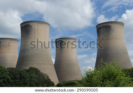 4 cooling towers at Fiddlers Ferry coal fired power station. Chimney stacks rise up above the greenery foreground. - stock photo