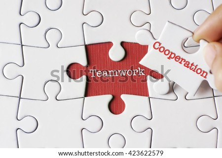 """Cooperation"" text on missing puzzle with a hand hold a piece of ""Teamwork"" text puzzle want to complete it - business and finance concept - stock photo"