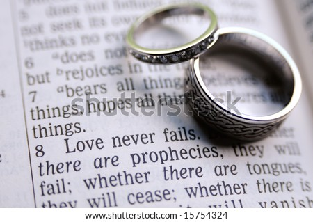 1 Corinthians 13:8 verse with two hand-crafted wedding rings in frame as well - stock photo