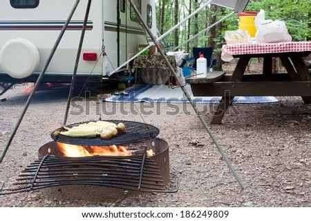 Corn and potatoes on an outdoor grill at a public park with a picnic table and camping trailer in the background. - stock photo