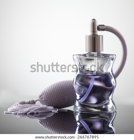 Cosmetic spray perfume on a gray background with reflection. - stock photo