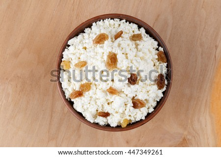 cottage cheese with raisins on a wooden table - stock photo