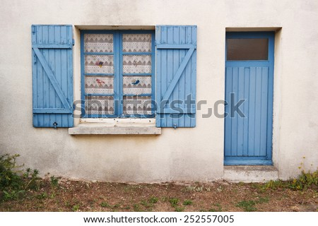 Cottage with traditional Breton blue window shutters and door in Brittany, France - stock photo