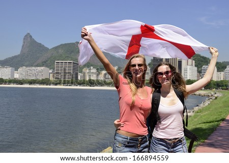 Couple of female sport fans holding the England flag in Rio de Janeiro with Christ the Redeemer in the background. - stock photo