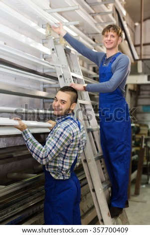 Couple of workers choosing window profiles at factory - stock photo