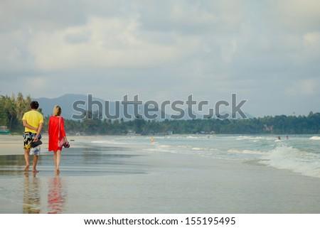 couple taking a walk on beach - stock photo