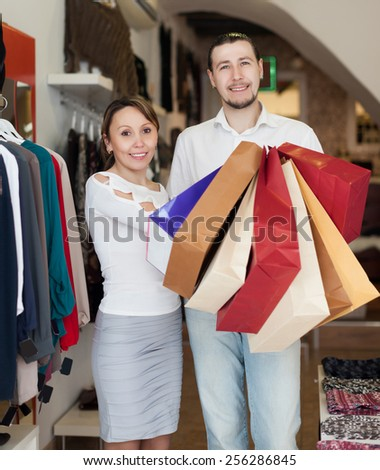 couple  with shopping bags at clothing store