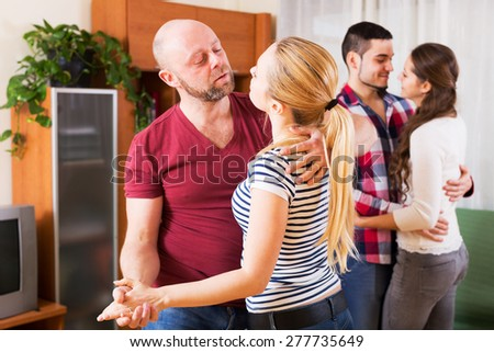 couples smiling and moving in slow dance at home - stock photo